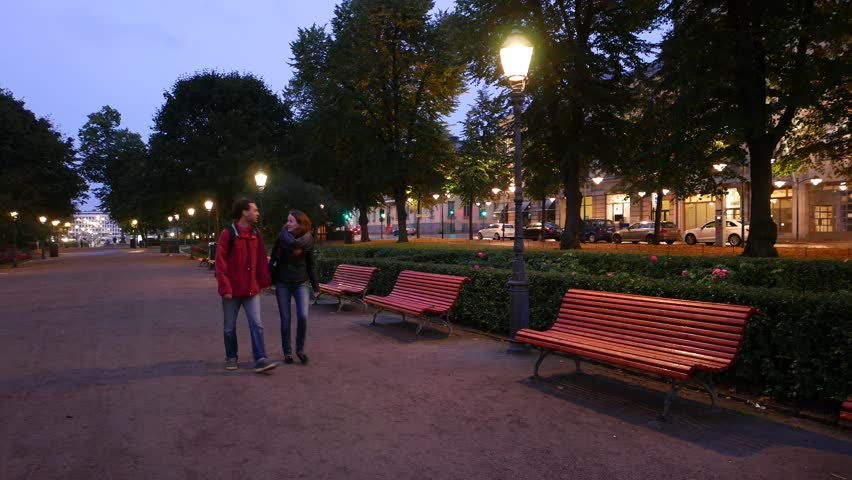Real romantic couple enjoy walk in evening espa park in Helsinki city. Young adult travelers stroll together, holding hands and slowly go along evening alley. Dusk view, nobody else at parkway | Shutterstock HD Video #25085666
