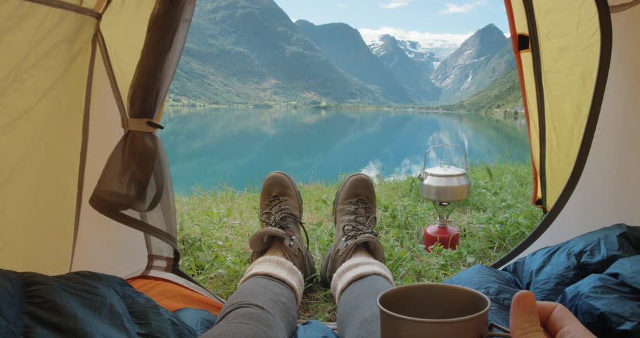 Camping woman lying in tent Close up of Girl feet wearing hiking boots relaxing on vacation POV #25095542