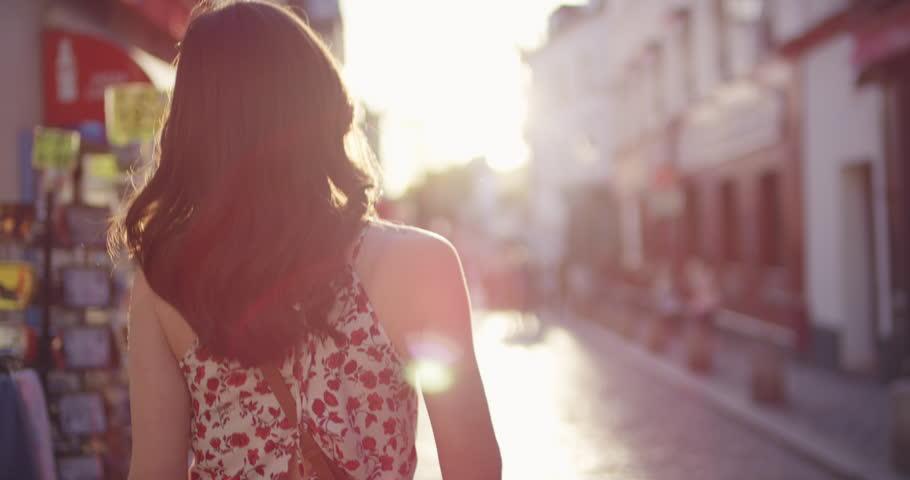 Rear view woman walking through European street at sunset wearing pretty floral summer dress sunshine lens flare confident girl exploring local Paris enjoying holiday travel vacation adventure