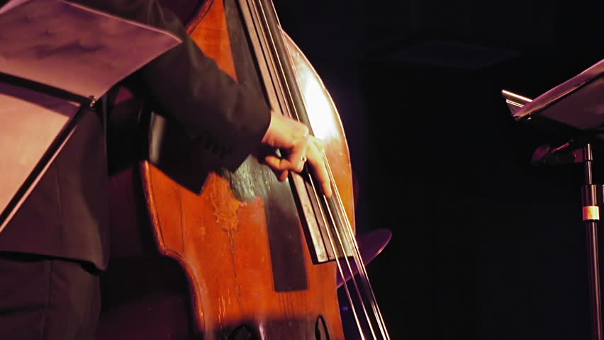 Contrabass player plays the double bass on the stage with sound lights. Jazz retro vintage concert performance entertainment. Close up shot with selective focus.