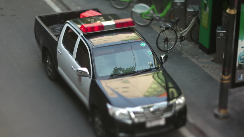 BANGKOK, THAILAND - MAY 2016: closeup view of law enforcement vehicle parked on road. Aerial view with miniature effect using Tilt&Shift lens   Shutterstock HD Video #25109477