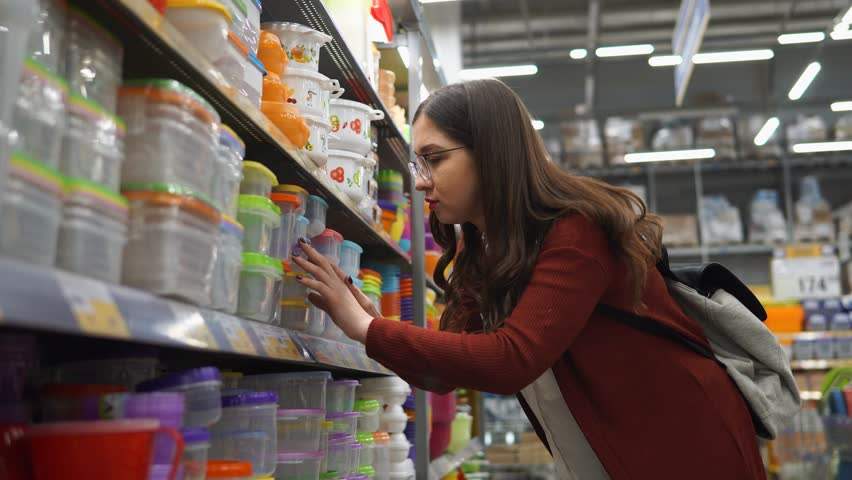 Young woman chooses a plastic lunch box in which the products remain fresh for a long time. She will put food and attributed it to work in this plastic boxes. #25113344