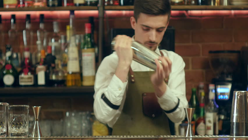 Barman shaking cocktail and pouring it to an empty glass at a nightclub | Shutterstock HD Video #25113752