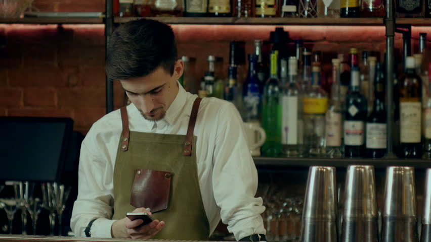 Bartender texting messages and smiling at work place   Shutterstock HD Video #25113863