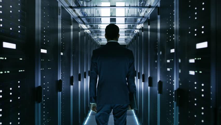 Data Center Technician Walking Through Server Rack Corridor Visually Inspecting Working Server Cabinets. Shot on RED EPIC-W 8K Helium Cinema Camera.