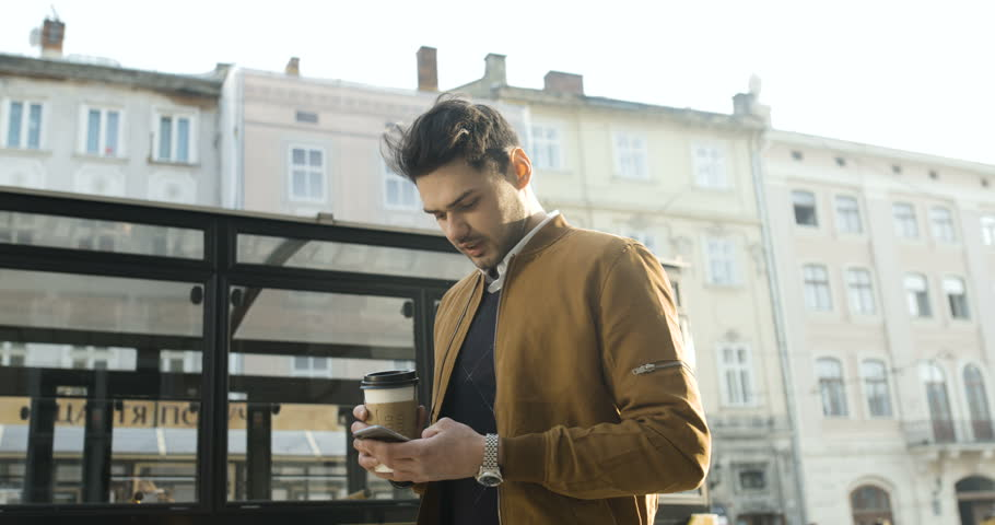 Attractive young man walking around the city using the phone and drinking coffee