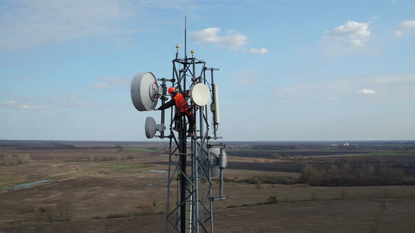 man working on radio telecommunication tower, radio master works at great heights of tv tower, industry of telecommunication engineering, drone flying around outdoor repeater base station tower Royalty-Free Stock Footage #25120934