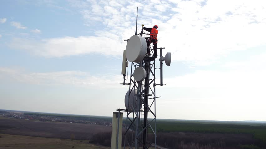worker servicing cellular antenna in front of sunlight, drone view of telecommunication antenna system, technician working on top of cellular antenna