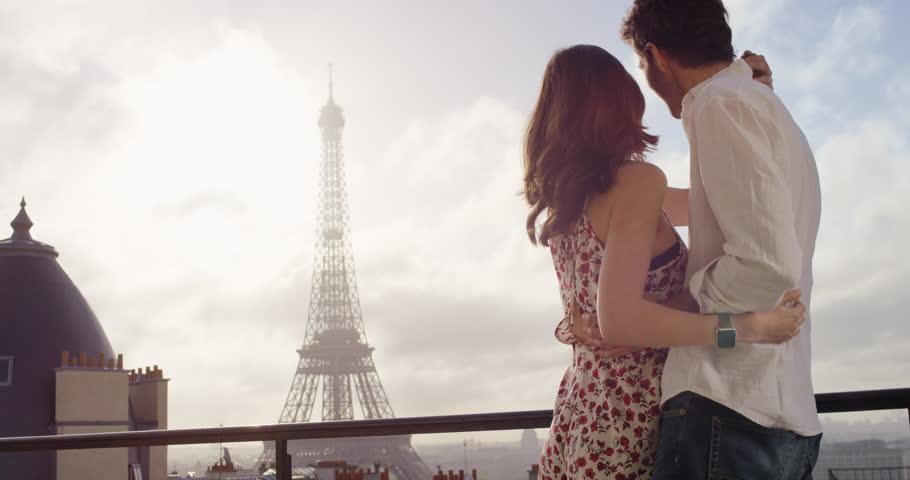 Romantic couple in Paris Eiffel Tower embrace kissing honeymoon enjoying European summer holiday travel vacation adventure