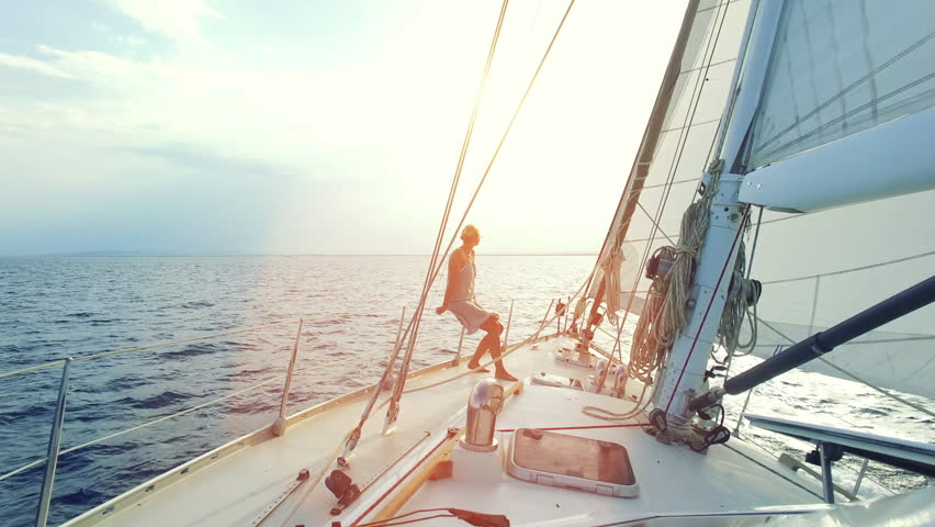 Mature adult woman is sitting on the front her big sailboat while cruising thru the ocean straight into the sunset on a sunny day on her lonely circumnavigation   Shutterstock HD Video #25125539