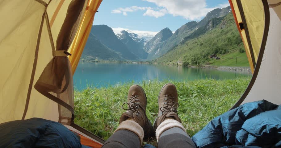 Camping woman lying in tent Close up of Girl feet wearing hiking boots relaxing on vacation POV #25126919