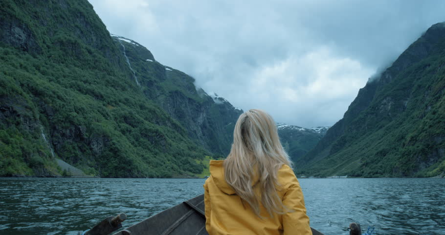 Brave Woman taking photograph in stormy weather on Fjord Norway with smartphone photographing scenic landscape nature background view enjoying vacation travel adventure | Shutterstock HD Video #25126922