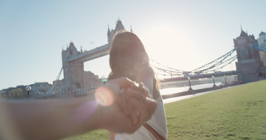 Young couple holding hands woman leading boyfriends walking towards Tower Bridge London POV travel concept
