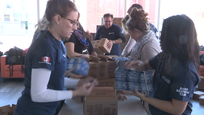 Toronto, Ontario, Canada March 2017 Aid workers in packaging supplies for victims in war ravaged Syria | Shutterstock HD Video #25140947
