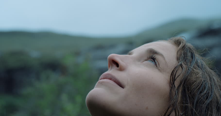 Close up portrait of Woman looking up at rain in nature with wet hair Hiker Girl trekking in Scotland Slow Motion #25164725