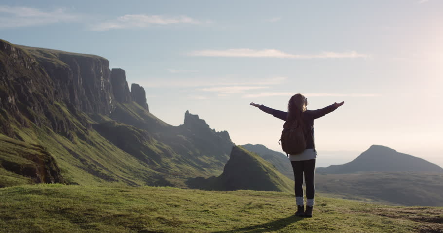 Woman with arms raised on top of mountain looking at view Hiker Girl lifting arm up celebrating scenic landscape enjoying nature vacation travel adventure Quiraing Walk on the Isle of Skye in Scotland | Shutterstock HD Video #25169498