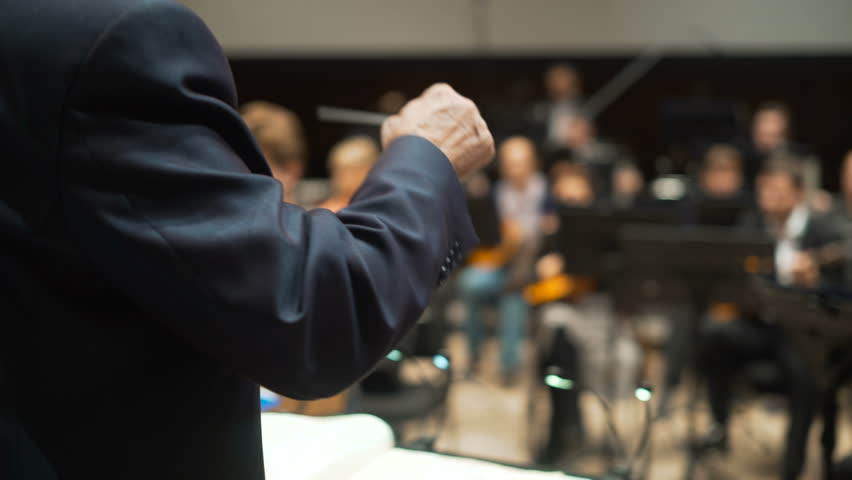 Famous elderly gentleman in suit is conducting band pit collective gesturing with wand or hand signs close up indoor Philharmonic Society. Supervision concept. Nonverbal communication. View from above | Shutterstock HD Video #25171223