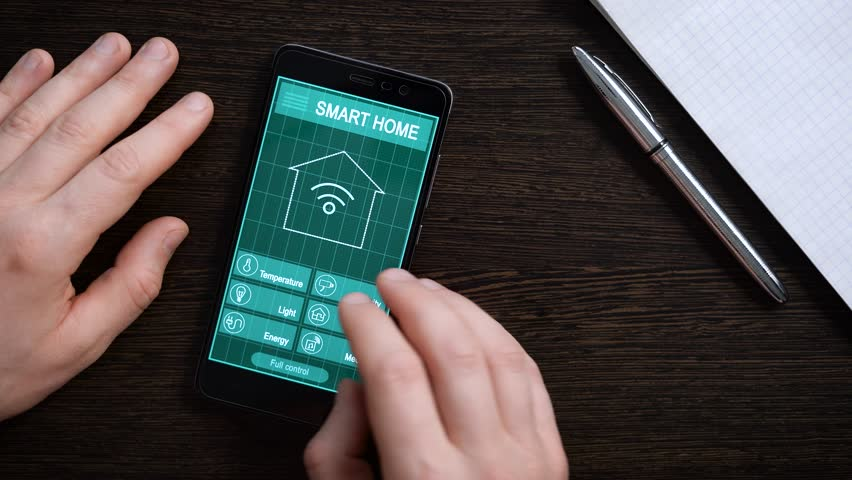 Remote home control system on a digital tablet or phone. The smartphone rests on a brown table with a wood texture. Man controls remotely the temperature, security systems | Shutterstock HD Video #25182458