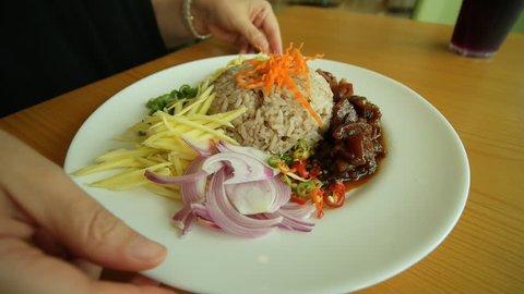 Thai food - Kao Cluk Ka Pi (Mixed Cooked Rice with Shrimp Paste Sauce) on white round dish.