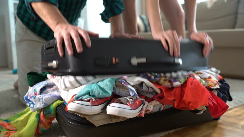 A couple is trying to close the chock-full suitcase. Close up