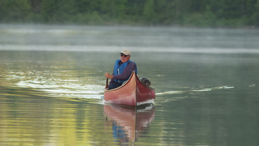 A man paddles his dog in a red canoe across the calm waters of Priest Lake.