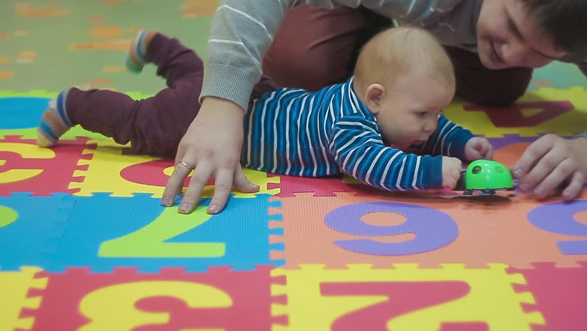 Spending Quality Time With a Baby Boy. Father and Son in Line Are Playing With Green Educational Toys. Learn Numbers With a Smart Handsome Little Gentleman Wearing Stylish Blue in Line Sweater Maroon #25215989