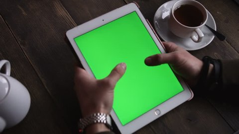Closeup hands man touching tablet computer with vertical green screen on the table is tea in a cafe