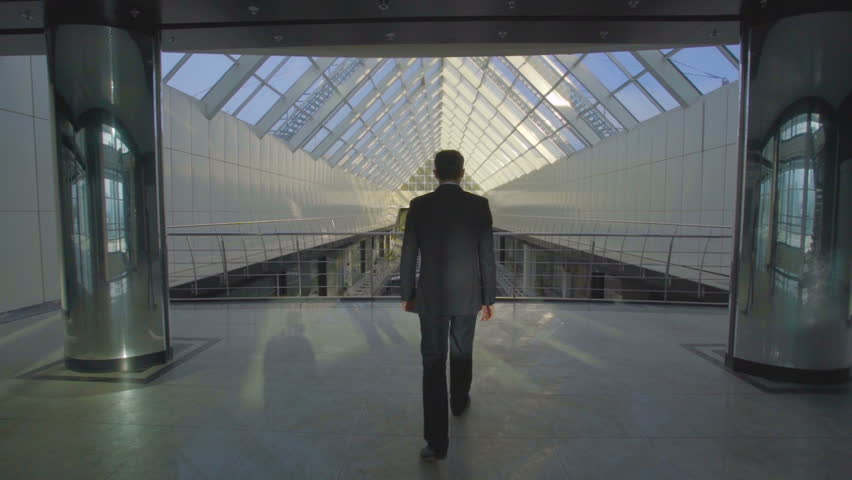 The businessman walk in the business center balcony. Slow motion