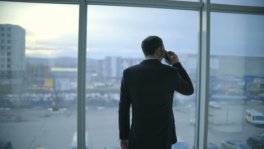 The businessman walk and phone near the panoramic window. Slow motion | Shutterstock HD Video #25232618