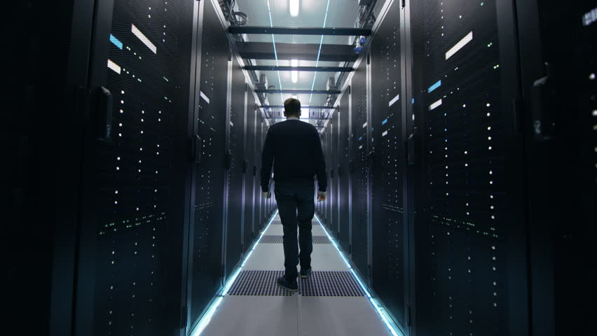 Following Shot of IT Engineer Walking Through Data Center Corridor with Rows of Rack Servers. Opens Laptop. Shot on RED EPIC-W 8K Helium Cinema Camera.