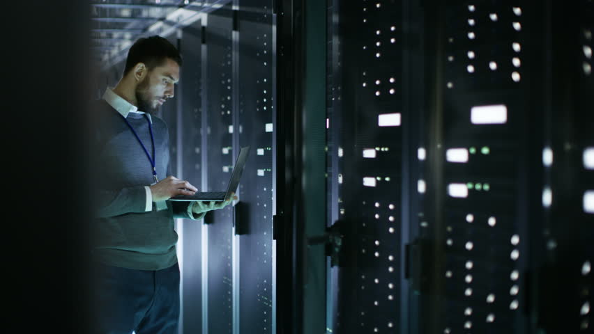 Male IT Technician Working on a Laptop Standing Before Open Server Rack Cabinet in Big Data Center. Shot on RED EPIC-W 8K Helium Cinema Camera.