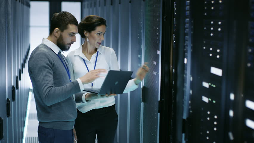 Male IT Specialist Holds Laptop and Discusses Work with Female Server Technician. They're Standing in Data Center, Rack Server Cabinet is Open. Shot on RED EPIC-W 8K Helium Cinema Camera. #25243136