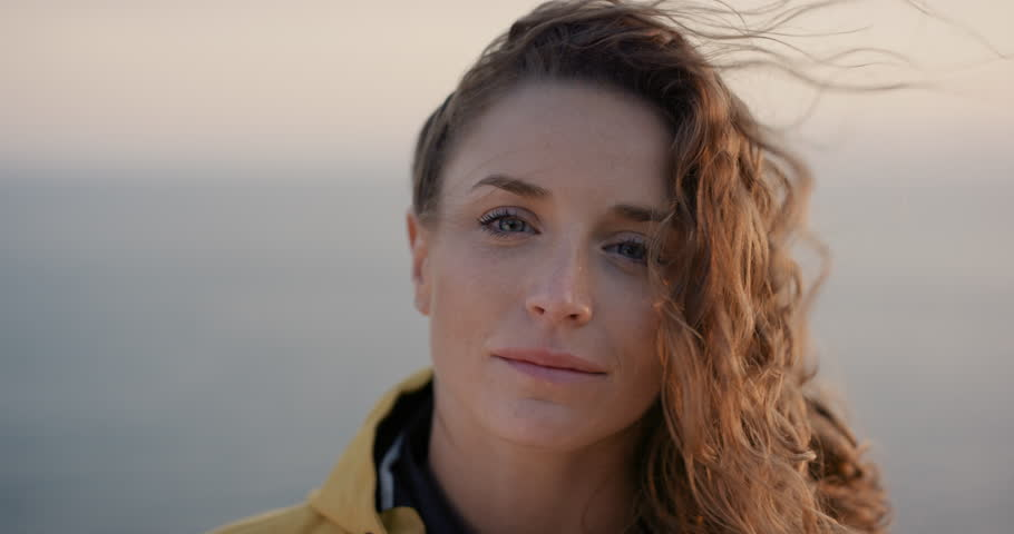 Close up portrait of Young Woman smiling with Red hair blowing in wind looking at sunset over ocean Girl wearing yellow raincoat trekking in Scotland Slow Motion Royalty-Free Stock Footage #25252820