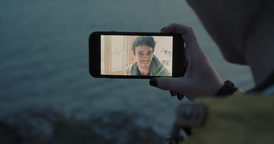 Close up Young woman having video chat holding smartphone  webcam chatting to friend outdoors by the sea | Shutterstock HD Video #25252886