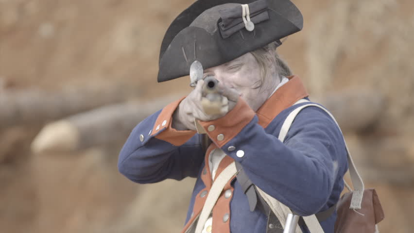 VIRGINIA - OCTOBER 2016 - American Revolution era Continental Patriot Soldier. Re-enactors, reenactment.  Firing Brown Bess musket gun with black powder and lead bullets in earthen fort in battle.
