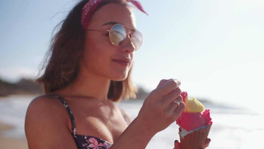 Young brunette hipster girl enjoying ice cream at beach in the summer