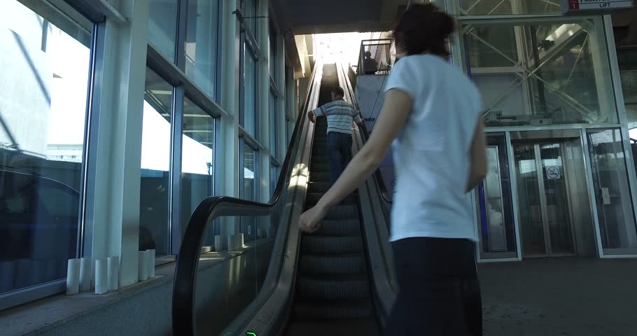 People stepping on escalator and moving upstairs towards the light, 4k #25291166