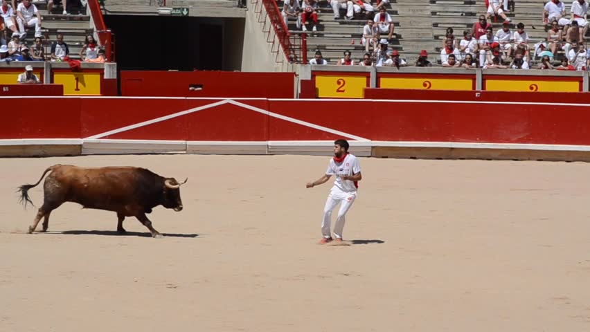 PAMPLONA, SPAIN - JULY 2016. A bull trimmer leaps over the head of the bull or twists his body as the bull passes by in the bull ring of Pamplona during San Fermin running of the bulls Festival