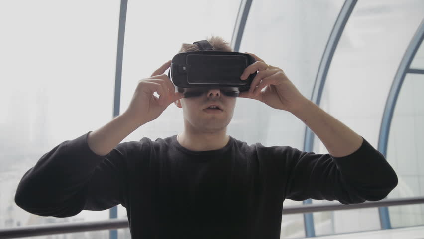 Technology VR - Mature businessman wearing virtual reality technology googles VR Glasses to work with in modern bright office. This new technology offers new 3D dimensions. | Shutterstock HD Video #25307942