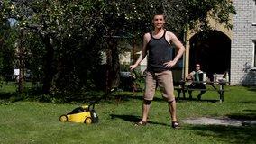 Young caucasian man mowing lawn by lawnmower. Freddie Mercury ''I want to break free'' parody. Funny, humor, humorous.