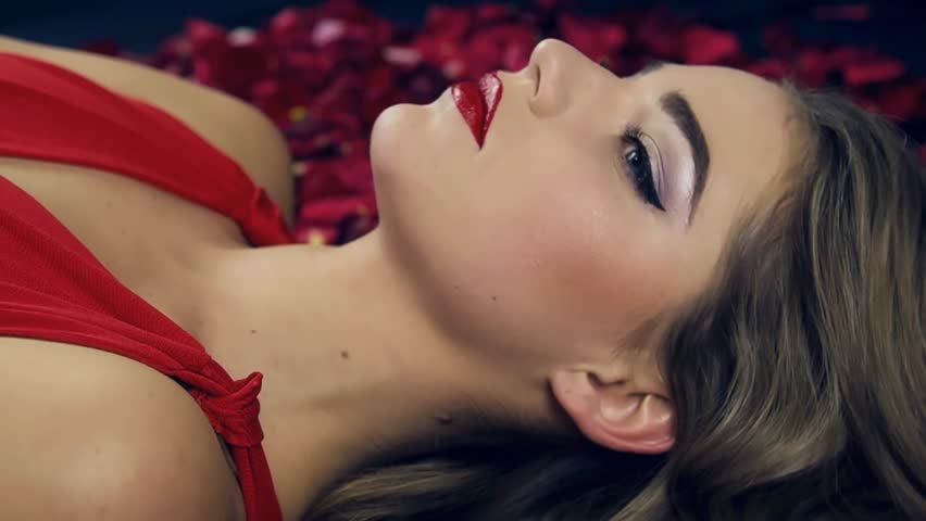 Girl in red dress with red lipstick on lips and bright makeup lies on the floor in studio among petals red roses. Turns her head slowly, looks into the camera, opens mouth, touches her body and hair.