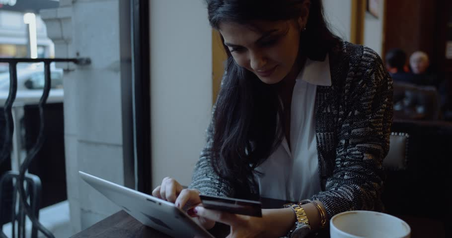 Young woman doing online shopping on tablet computer in cafe. Happy girl. | Shutterstock HD Video #25329599