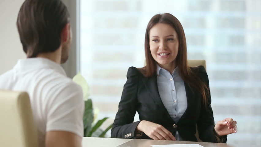Young happy beautiful businesswoman consultant wearing formal suit meeting casual client at modern office. Two colleagues or partners negotiating, working with documents. Young man reading contract  #25331183