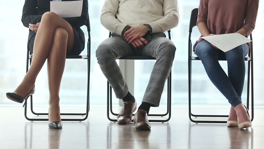 Ready to get new career. Group of three young businesspeople sitting on chairs in office, waiting and going for job interview, feeling nervous. Body language. Close up of legs. Job search concept | Shutterstock HD Video #25331192