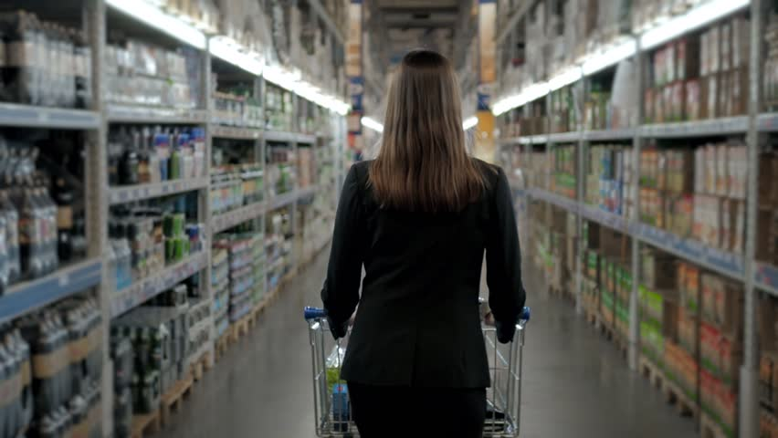 Young woman shopping at supermarket. Thinking what she should buy next, walking with trolley near wine shop | Shutterstock HD Video #25334972