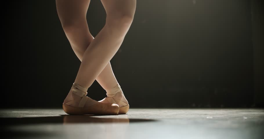Close-up of ballerina feet in pointe shoes dancing ballet elements, slow motion