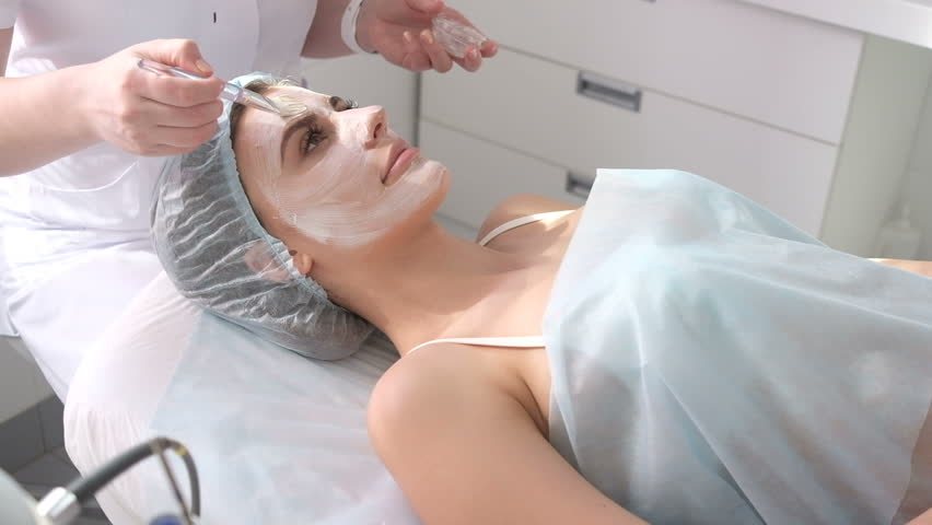 Woman with facial mask at beauty salon. face treatment. Skin care. Young Woman getting a cosmetic medicine treatment, close-up. Beautician hands at work, applying facial mask on a beautiful face