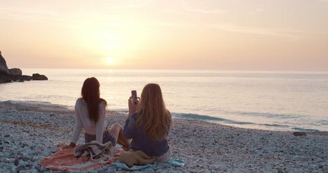 Two girl friends taking photograph of sunset on empty beach smartphone women photographing sunrise scenic landscape nature background view enjoying vacation