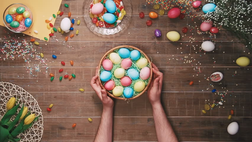 Man rotating basket with easter eggs on table decorated with easter eggs. Top view | Shutterstock HD Video #25343000