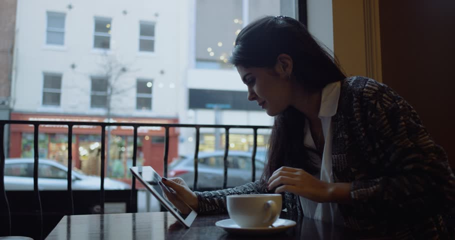 Young woman with tablet computer sitting in cafe. Slow Motion. Shot on RED Cinema Camera | Shutterstock HD Video #25354406